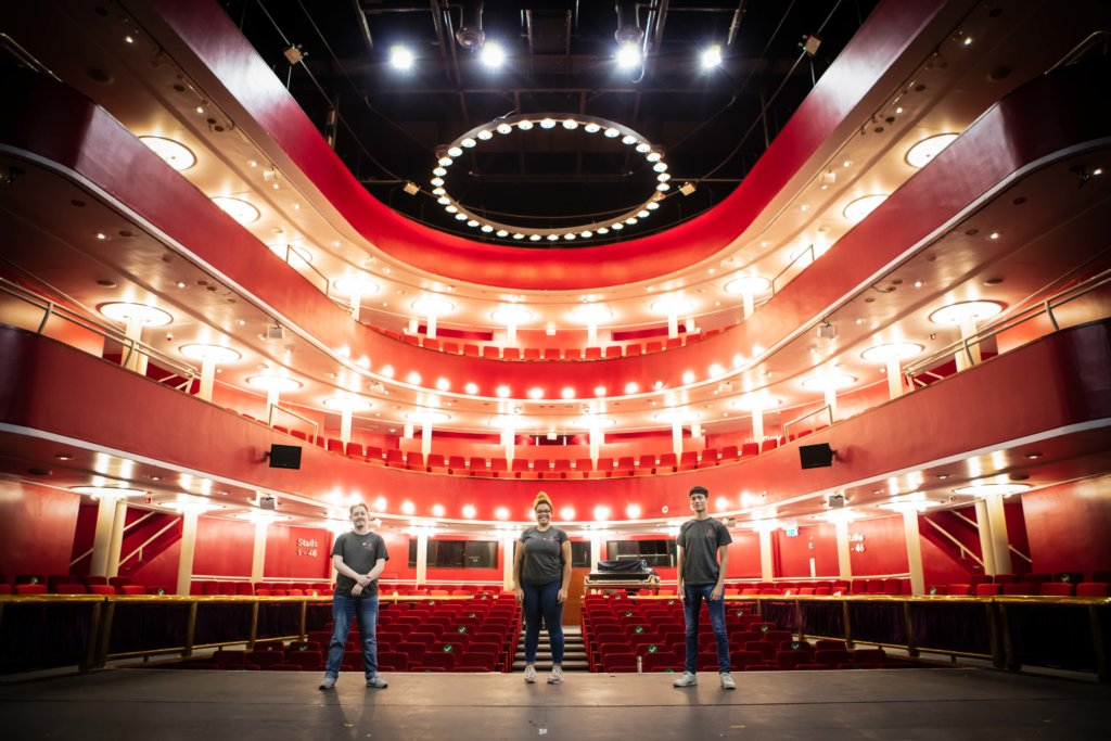 John Anthony Craig, RCS Student President, stands on the stage of the New Athenaeum Theatre with vice-presidents Zweyla Mitchell dos Santos and Ken Fairbrother