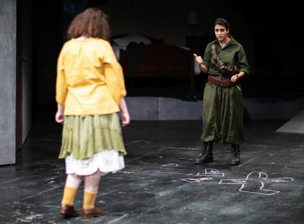 A performer dressed in military wear stands questioning another female performer, wearing a yellow jacket